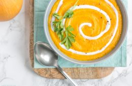 spicy pumpkin and carrot soup in a bowl, with light blue napkin and wood board beneath, small pumpkin on the left side