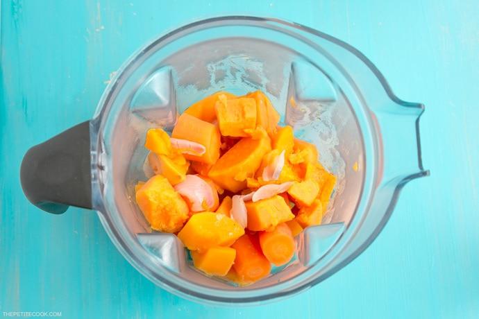 pumpkin, onion, carrots in the jug of a vitamix