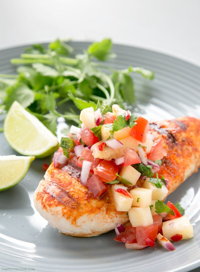 tequila grilled chicken breast with pineapple salsa on top served on a plate with greens and lime