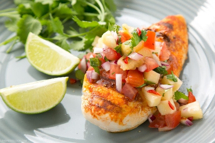 tequila lime chicken topped with pineapple salsa, served lime wedges and cilantro on the side on a grey plate