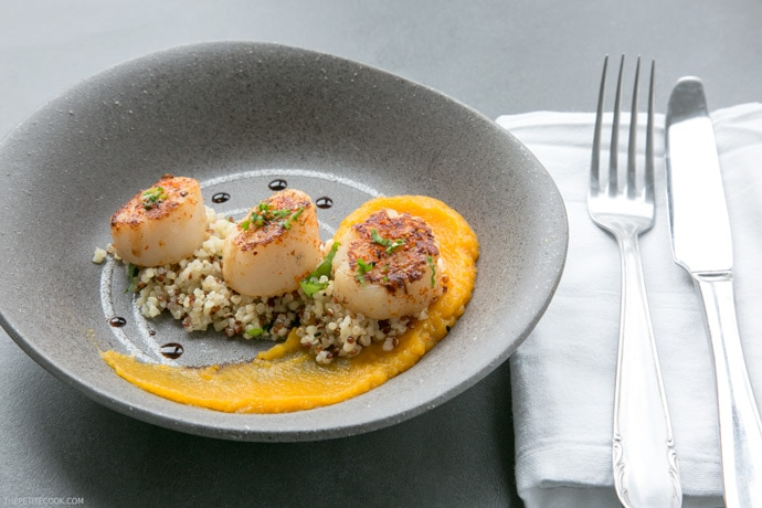 spicy scallops with pumpkin puree in a grey plate with fork and knife on the side on a white napkin