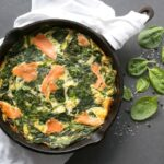 Crustless quiche with salmon and spinach in a cast iron skillet over a white napkin, next to the skillet spinach leaves, salt and pepper scattered over