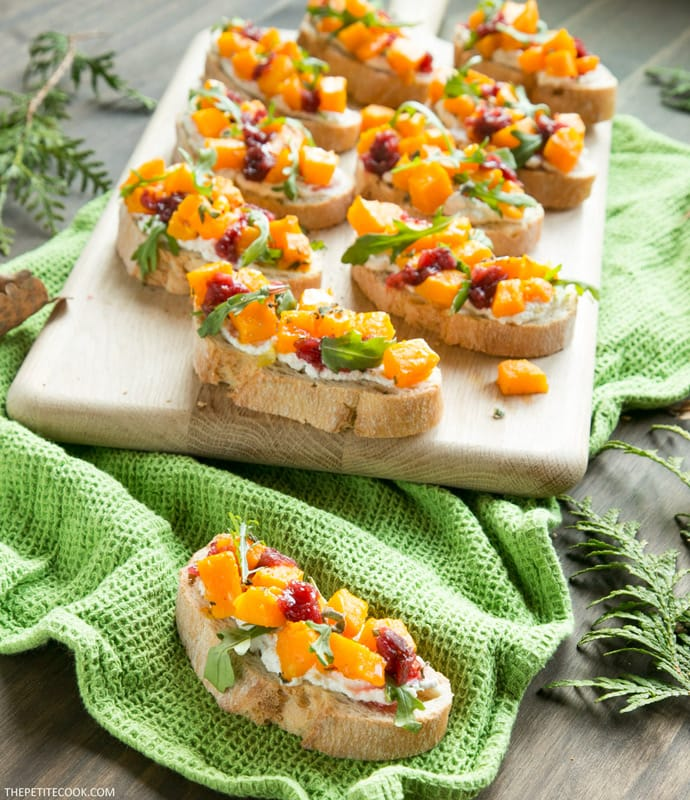 roasted pumpkin bruschetta on wood board and on green kitchen cloth