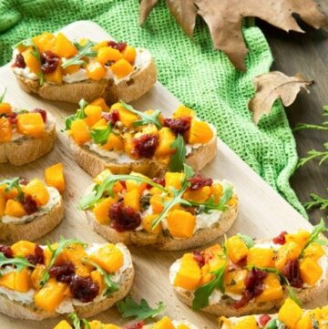 roasted pumpkin bruschetta over wood board with a green cloth on the right