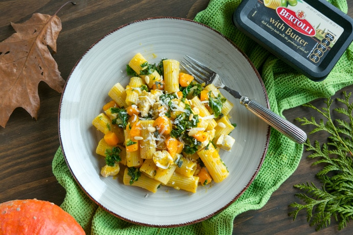 pasta with pumpkin chicken and kale on a plate with a fork, Bertolli spread packaging on the right