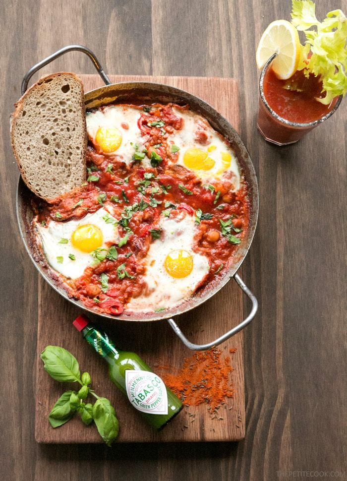 Easy Shakshuka in a large skillet with toasted bread slice on the side, on wood board decorated with spices, green tabasco bottle, and basil leaves. Bloody mary glass on the side.
