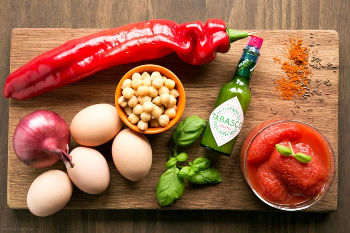 Easy shakshuka ingredients on wood board: one red onion, one long bell pepper, four eggs, a small cup with chickpeas, basil leaves, green tabasco bottle and cup with canned whole tomatoes.
