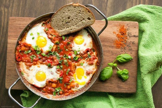 Easy Shakshuka in a large skillet with toasted bread slice on the side, on wood board decorated with spices and basil leaves.