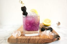 brambe cocktail in a glass topped with 2 blackberries and two lemon slices, over a wood board with crushed ice, blackberries, half lemon.