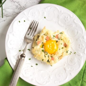eggs in a cloud on a white plate with fork, over a green napkin