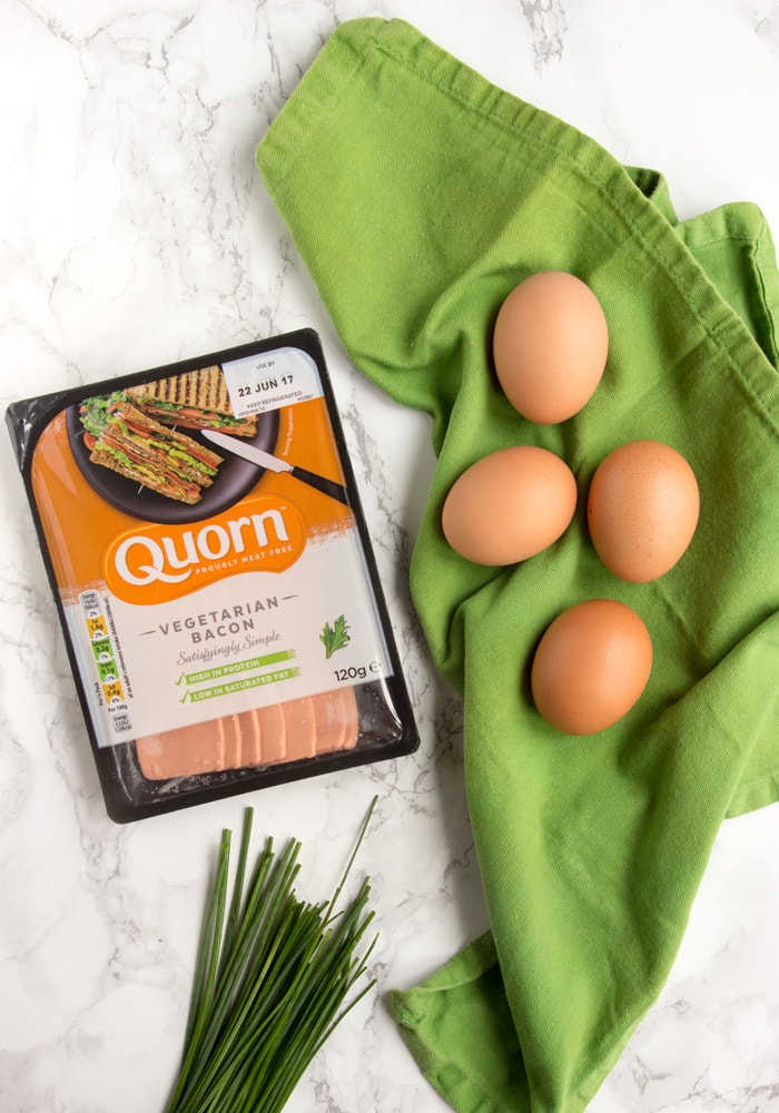eggs on a green napkin, chives on the bottom side and quorn vegetarian bacon packagin on the left side