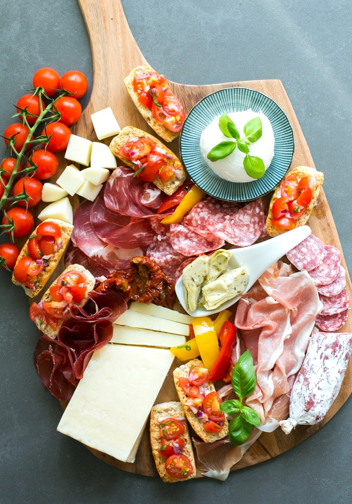 Aperitivo platter featuring mozzarella ball, cured meats, bruschetta, artichokes in olive oil, and  cubed cheese.