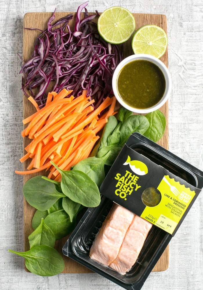 sliced purple cabbage, carrots, spinach leaves, halved lime, the saucy fish co salmon fillets in packaging and a small white pot with cilantro dipping sauce, all placed on a wood board.