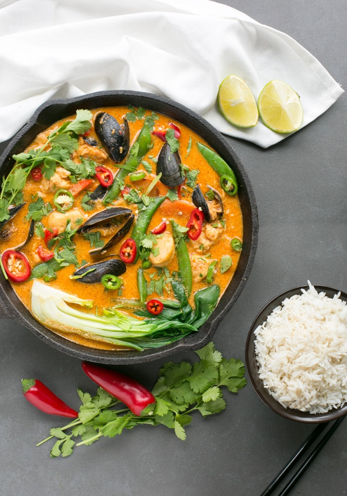 Thai Red Fish Curry in cast iron skillet, next to fresh cilantro, red chili peppers and halved limes, a small bowl with rice and black chopsticks.