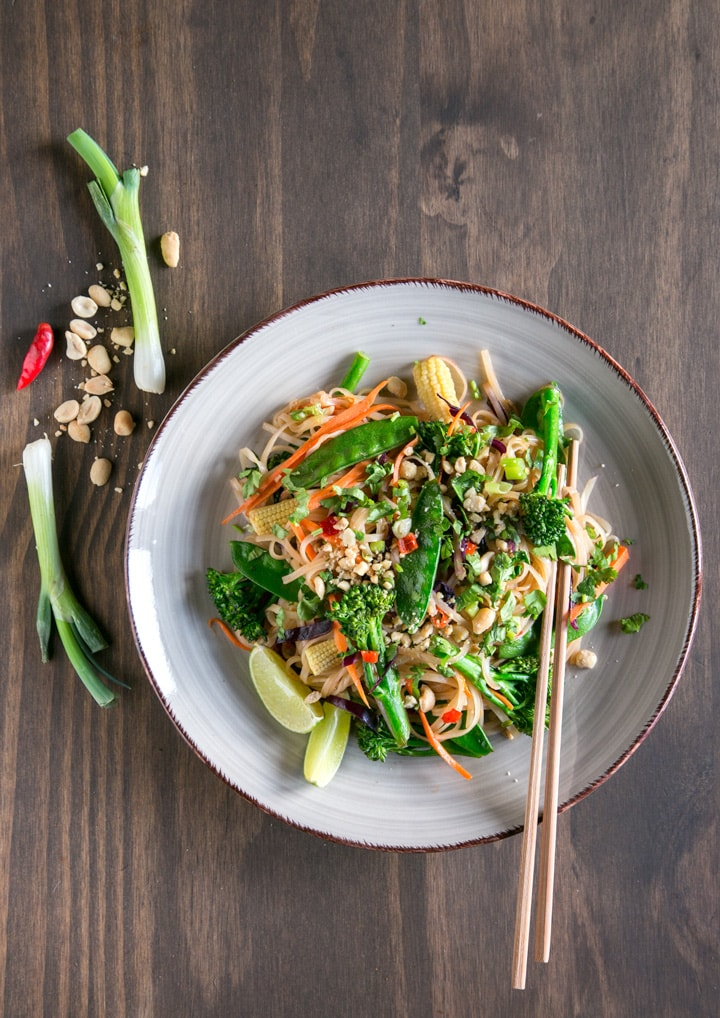 Pad thai with vegetables topped with roasted peanuts and served with lime wedges.