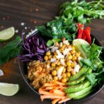 chickpea and freekeh buddah bowl with sliced avocado and carrots and salad leaves.