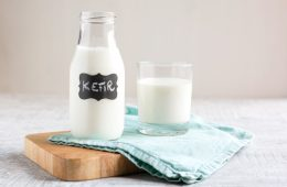 Homemade kefir in small glass bottle next to a glass with kefir, over light blue napkin and wood board