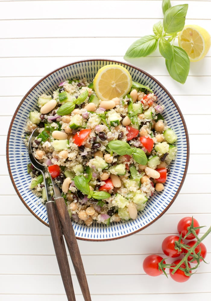 quinoa and bean salad topped with half lemon and lemon leaves in a large bowl with serving spoons.
