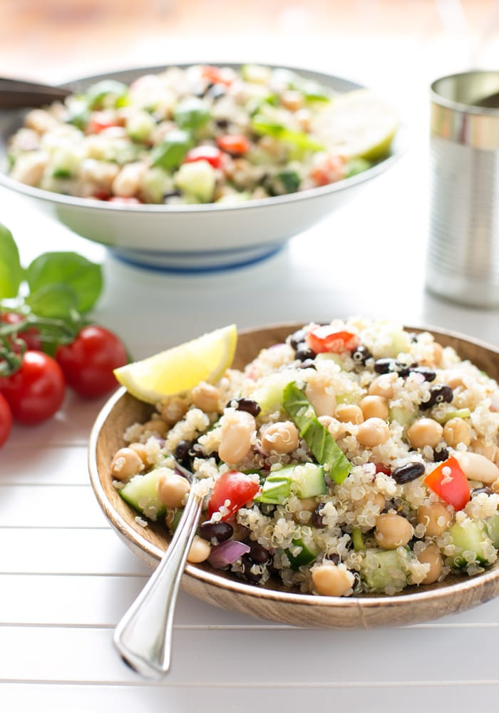 quinoa and bean salad topped with half lemon and lemon leaves in a serving plate with a fork, more salad in a bowl in the background.