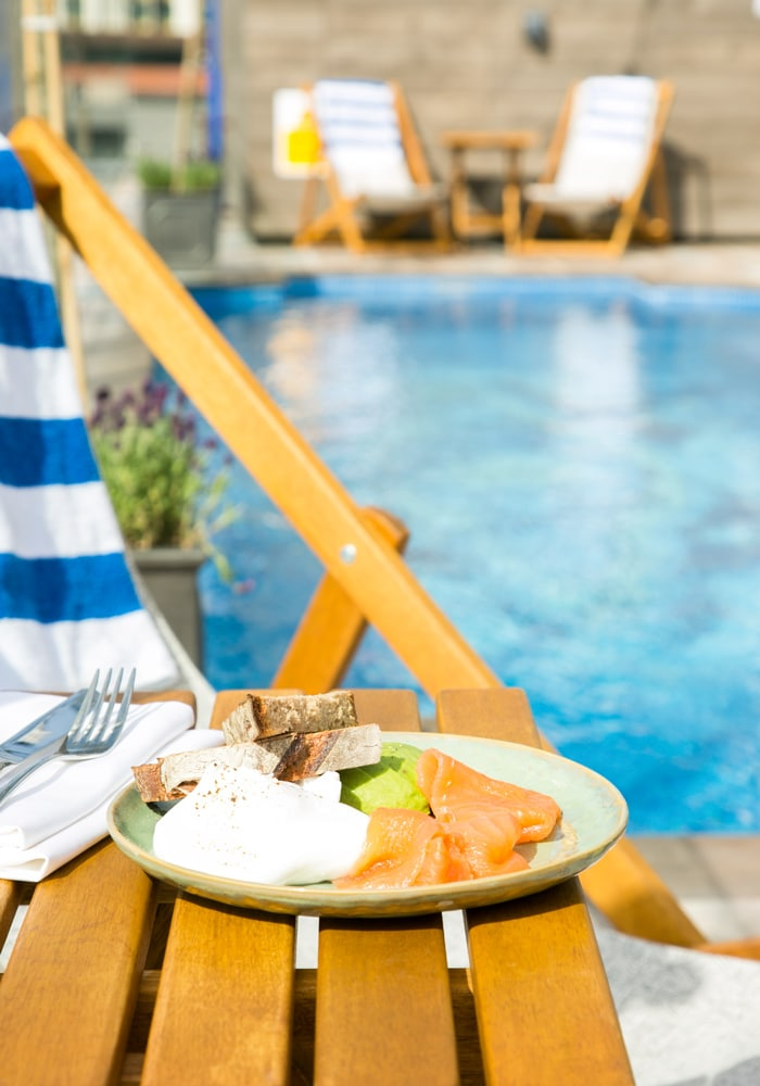 plate with poached eggs, salmon, avocado and bread on a table overlooking the pool