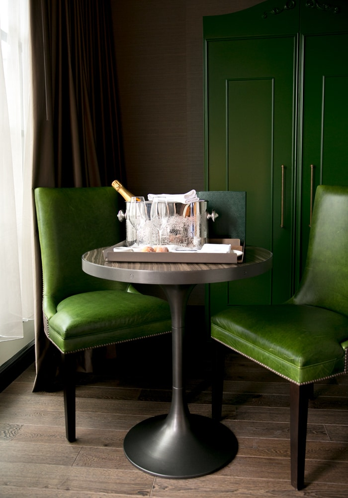 green chair and small table with tray two glasses and champagne in a ice bucket