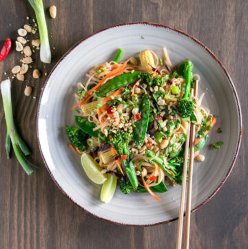 vegan pad thai topped with roasted peanuts and served with lime wedges and chopsticks.