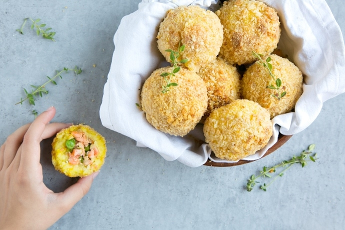 salmon and pea baked arancini rice balls in a dish covered with white napkin, on the left side hand holding half arancini ball