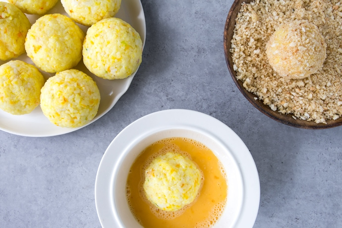 rice balls on a plate, rice ball dipped in whisked eggs on a plate, rice ball rolled into breadcrumbs on a plate