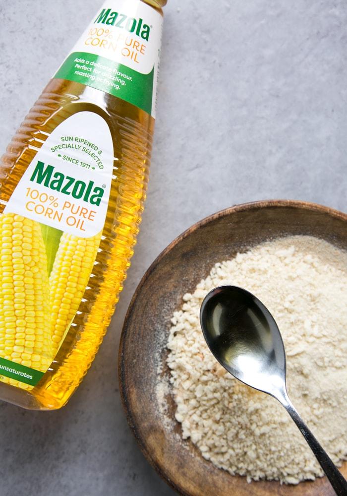 mazola oil bottle, oil in a spoon and panko breadcrumbs on a plate