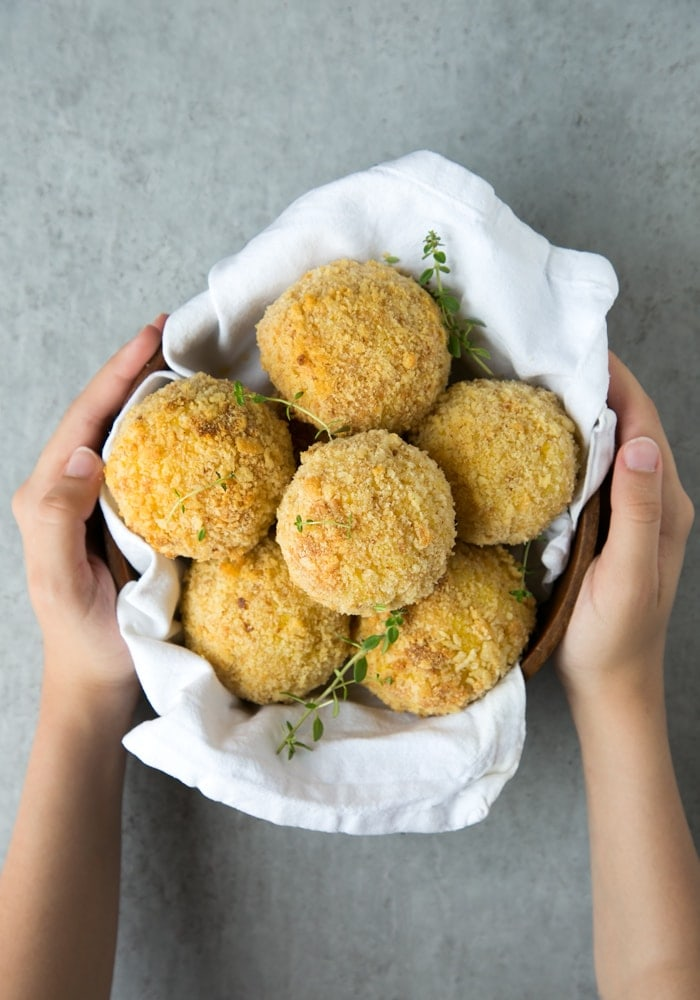 hands holding a bowl covered with a white napkin and filled with salmon and pea baked arancini balls