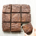 espresso brownies cuto into squares and arranged into a grid. Hand holding the left down corner brownie.