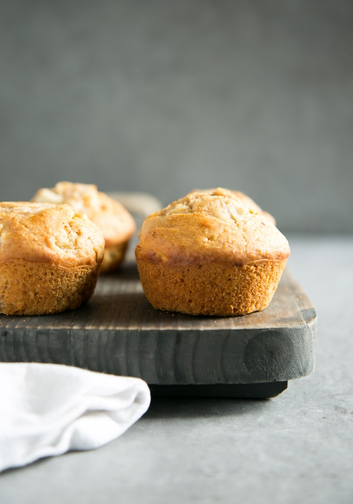 peach muffins on a wood board and white napkin on the left side