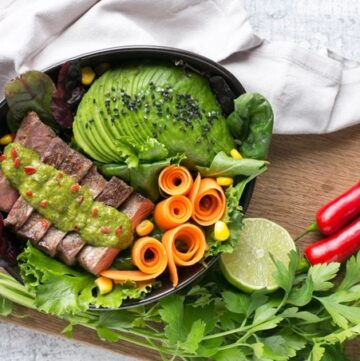 steak salad bowl with carrot, salad leaves,Avocado, steak topped with chimichurri sauce