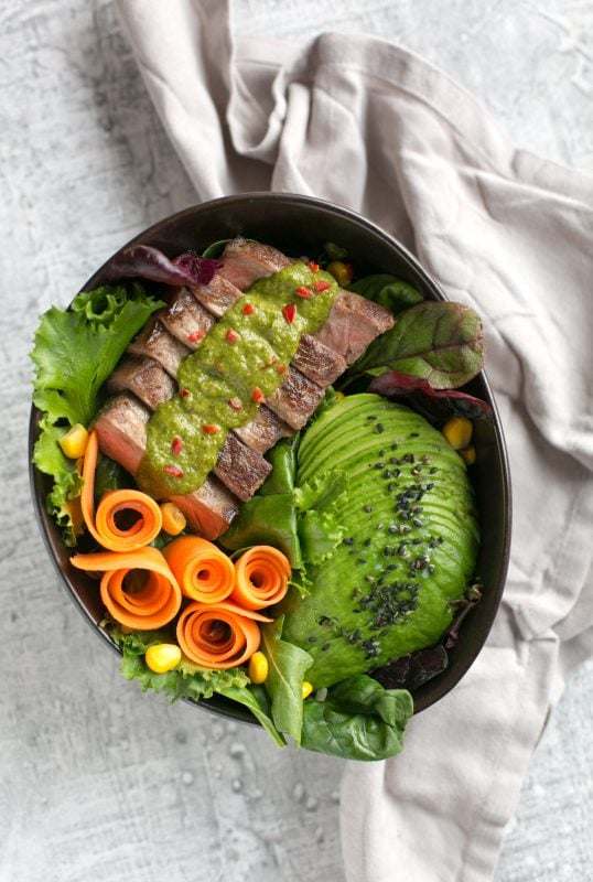 steak salad bowl with carrot, salad leaves, avocado, steak topped with chimichurri sauce