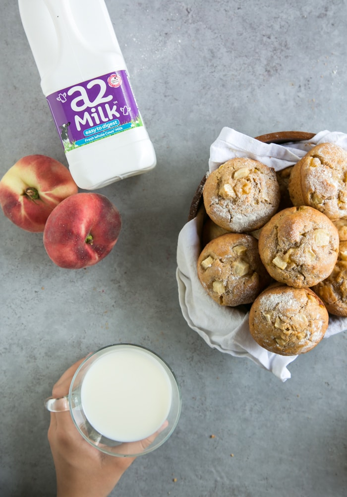 peach muffins, a2 milk bottle, 2 peaches, hand holding a cup of milk