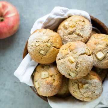 peach muffins in a bowl and 2 peaches on the background