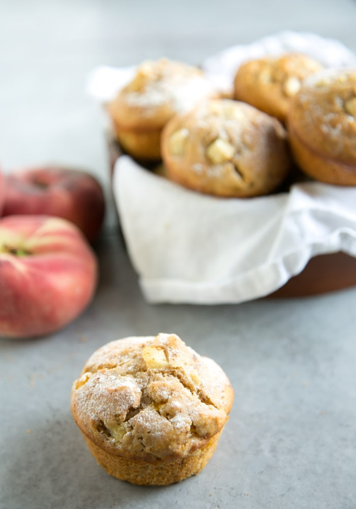 peach muffin on focus and peach muffins in a bowl on the background, 2 peaches in the background