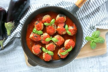 Vegetarian Aubergine Meatballs in pan over striped napkin and wood chopping board, basil leaves on the top right corner.