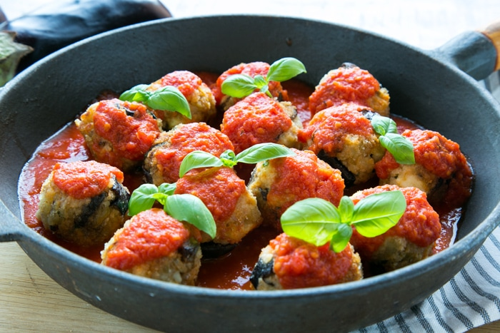 Vegetarian Aubergine Meatballs topped with tomato sauce and basil leaves in a large cast iron skillet over striped napkin, side view.