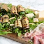 eggplant roll-ups on a bed of rocket leaves next to prosciutto slices and grana padano cheese chunks all placed on a wood board