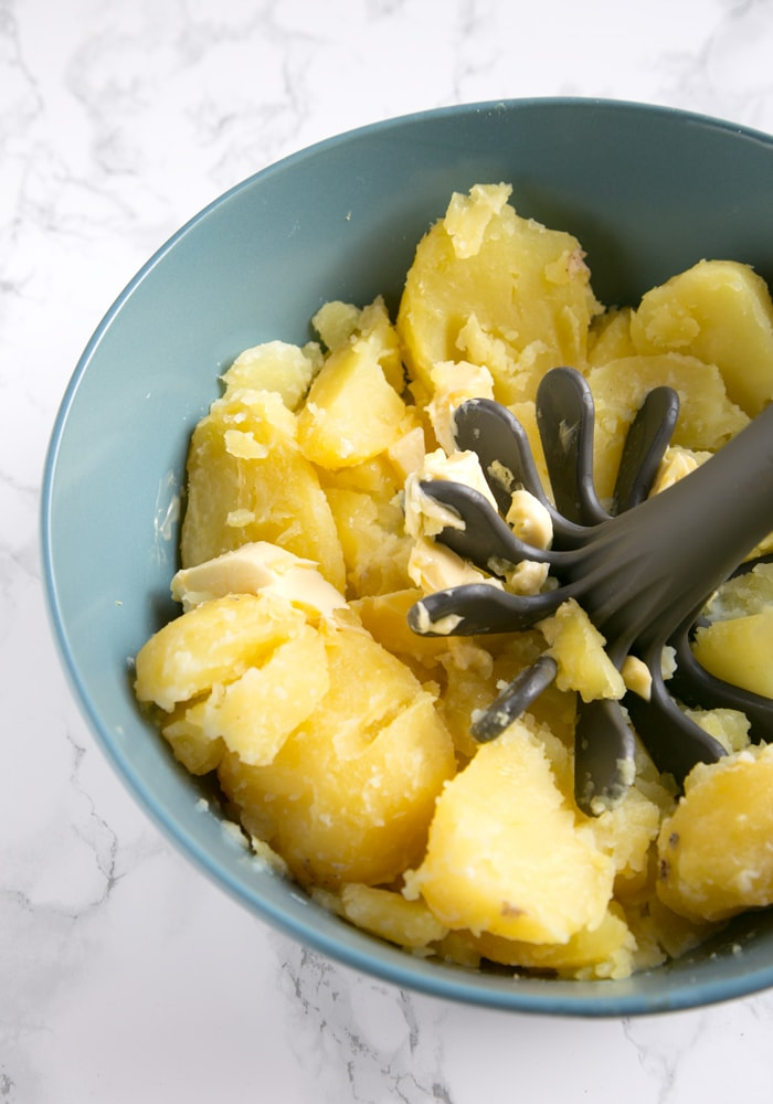 recipe step 1: boiled potatoes in a bowl, with softened butter and potato masher
