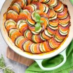 Ratatouille in a large green cast iron shallow pan, bunch of thyme sprigs on the left side and a green napkin on the top right side.