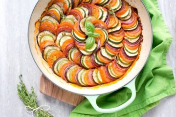 Easy Ratatouille in a large green cast iron shallow pan, bunch of thyme sprigs on the left side and a green napkin on the top right side.