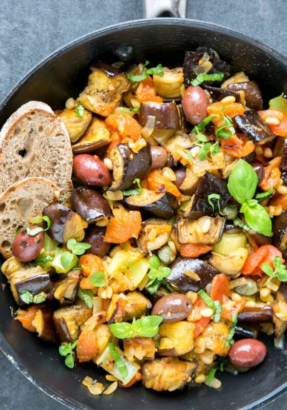 eggplant caponata in a skillet served with crusty bread slices