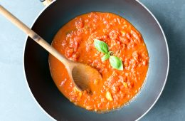 italian tomato sauce in skillet with wooden spoon and basil leaves