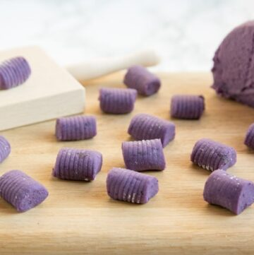 Purple homemade potato gnocchi on a wood board, next to the dough and gnocchi wood board.