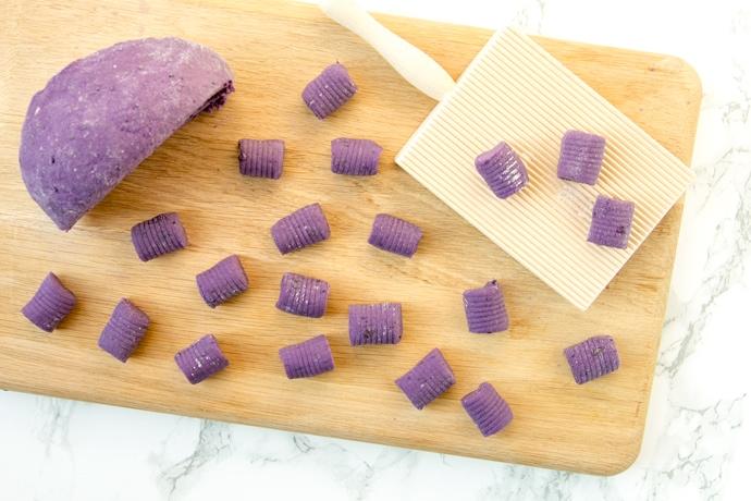 Homemade purple potato gnocchi on a wood board, next to the dough and gnocchi wood board.