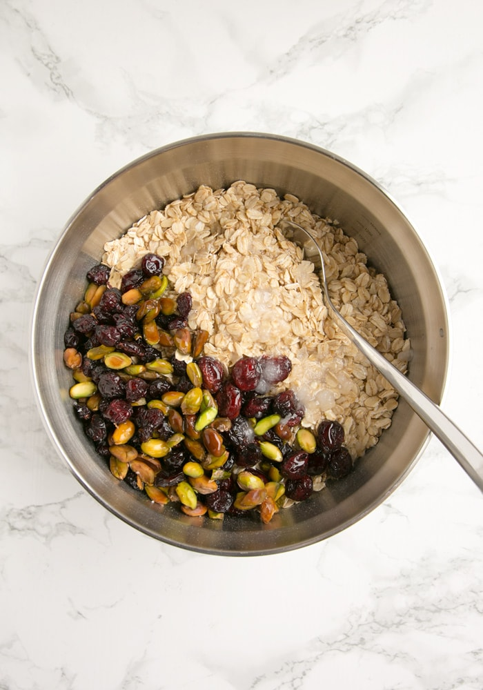 bowl filled with pistachio, cranberries, oats and sugar.