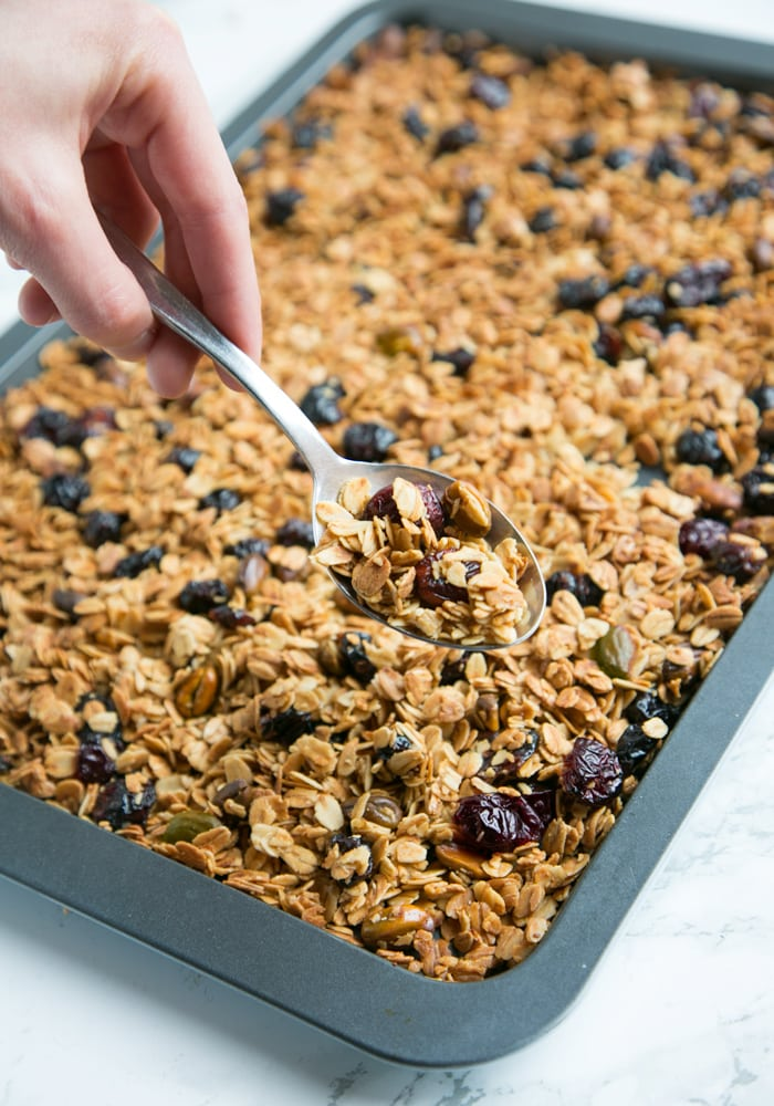Hand holding a spoon filled with Christmas homemade granola, over a tray filled with more granola.