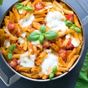 caprese pasta bake in a large baking pan, topped with mozzarella and basil leaves